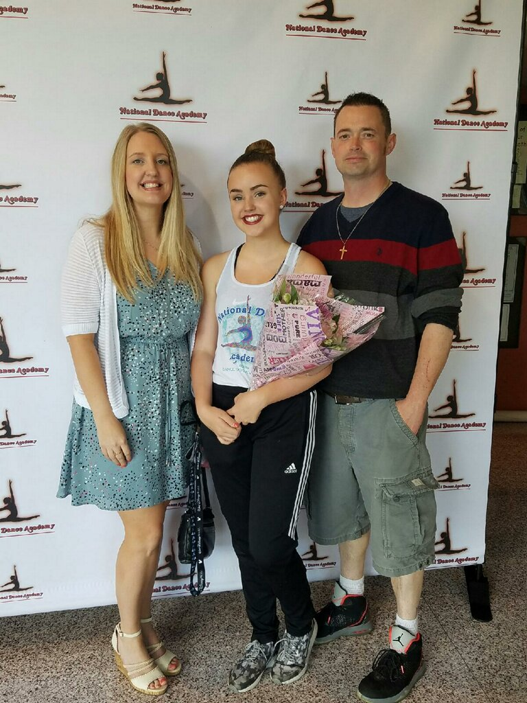 Lair standing with her parents after a dance competition.