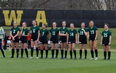 The girl's varsity soccer team laughs before getting ready for the National Anthem.