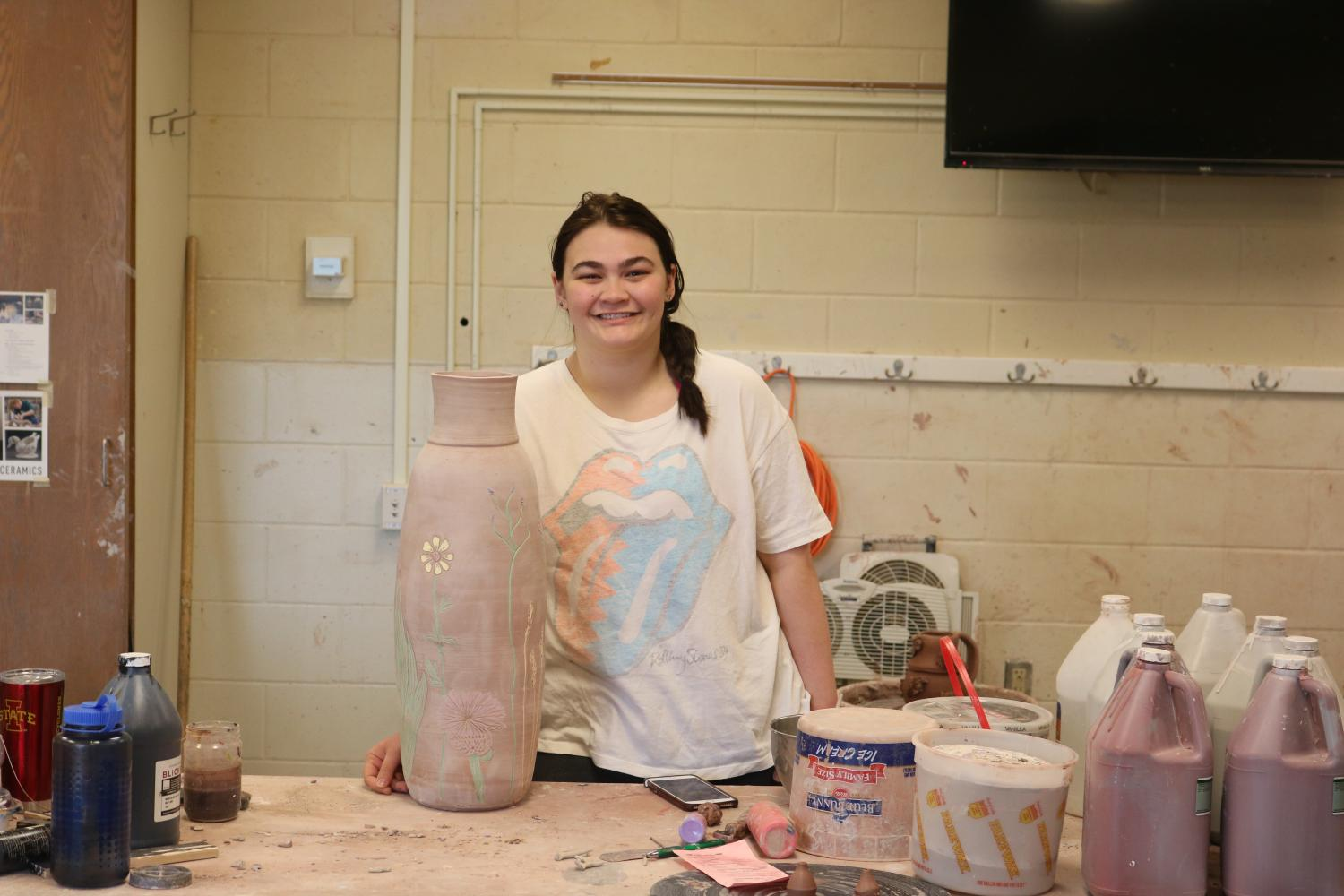 Olivia Benda '19 stands in front of her flower vase surrounded by materials used to make it in the ceramics room on May 1.