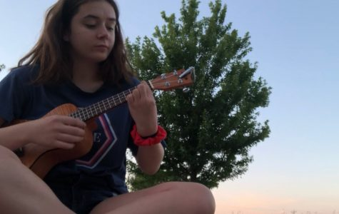 Tess DeGrazia '23 playing her ukulele outside.