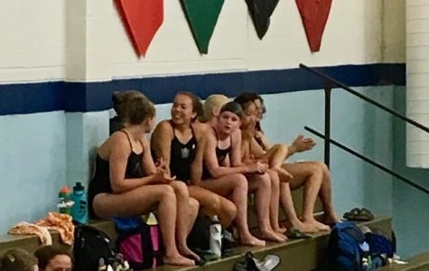 Jessica Nauman '23 and her swimming teammates are sitting on a bench during a swim meet.
