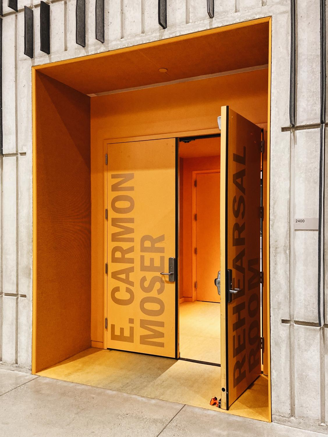 The+bright+orange+entrance+to+the+E.+Carmon+Rehearsal+Room+pops+against+the+Voxman%E2%80%99s+gray+walls.+Music+spills+into+the+hallway+as+several+college+students+practice+their+band+instruments.+%28framing%29%0A