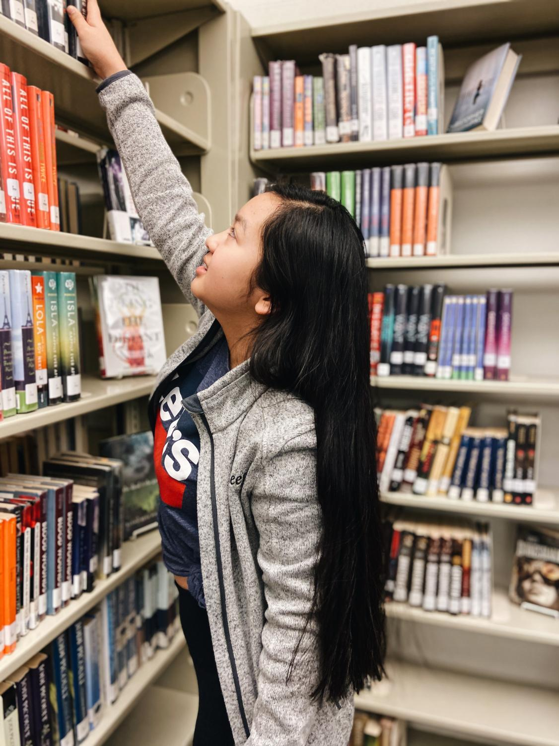 Kevy+Huynh+%E2%80%9823+searches+the+fiction+section+of+West+High+Library+for+her+next+read.+%28portrait%29