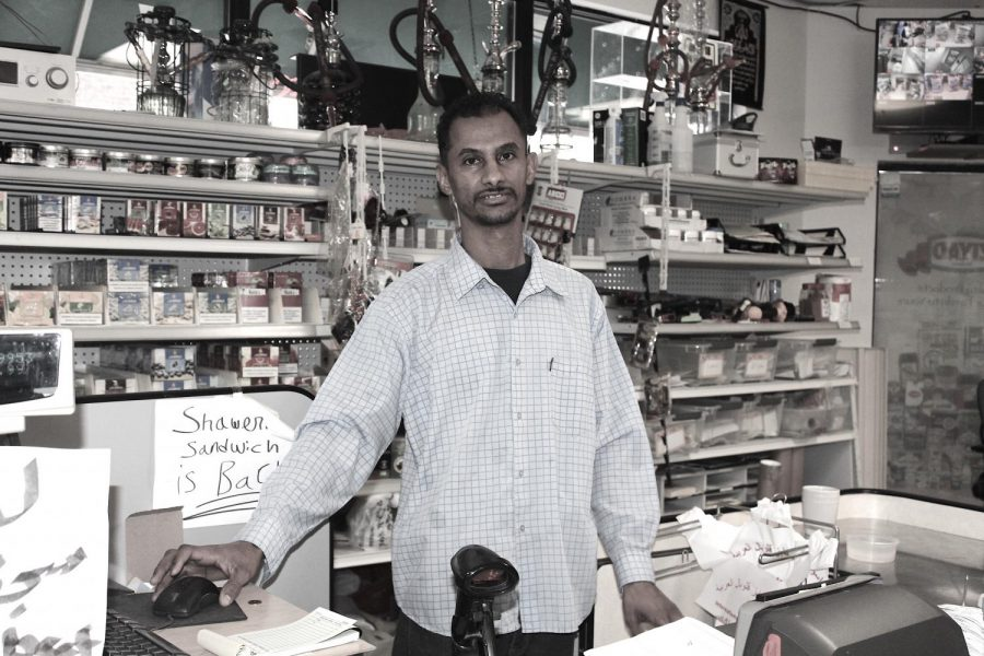 """The man working cash register at the Global Market. """"I meet all kinds of people at the market,"""" - man said. """"Poor or rich, you will always will receive respect."""""""