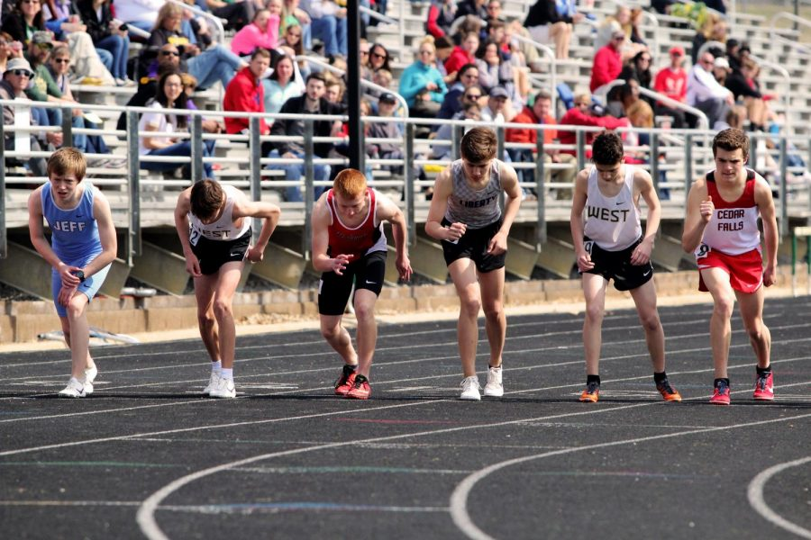 Alex Mckane '22 (second from the left) and Nicolo Schianchi '22 (fifth from the left) jolt to the start line before the gun of the 3200 meter race at the first annual Eastern Iowa Track Festival on April. 6. at Trojan Field.