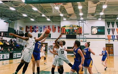 Matayia Tellis '21 and Meena Tate '23 reach for the rebound in a game against Dubuque Wahlert on Jan. 28. (event and featured image)