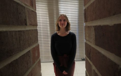 Zoe McLaskey '22 stands behind the brick pillars in the West High commons.  (Framing)