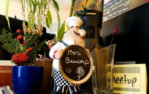 A photo of a French Chef Statue holding a sign saying 'Merci Beaucoup'.