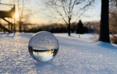 A glass orb sitting on the icy, frozen ground during a beautiful sunset.