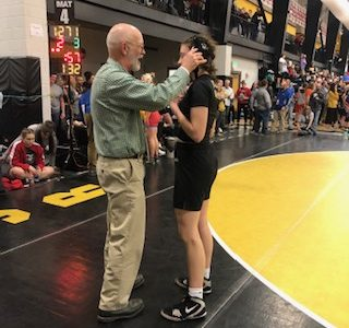 Coach Mike Haverkamp adjusts Emma Dunlap '22's headgear after her wrestling match at the State tournament on Jan. 26th. (Feature)