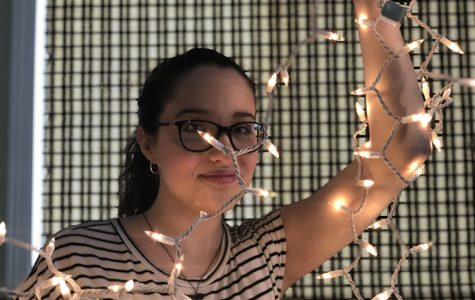 Willow Oleson '23 holds up lights in a dark room. The glow from the lights illuminates the room and herself.